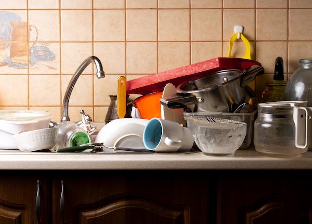 Un sacco di piatti sporchi giacciono nel lavandino della cucina che deve essere lavato.
