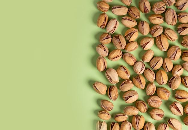 Un sacco di pistacchi fritti su uno sfondo verde, vista dall'alto, distesi, copia spazio.