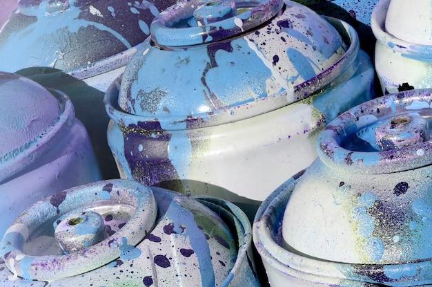 Un sacco di serbatoi di metallo blu usati con vernice per disegnare graffiti