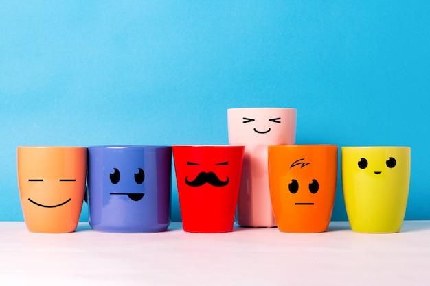 Un sacco di tazze colorate con facce buffe su uno sfondo blu. il concetto di compagnia amichevole, famiglia numerosa, incontro di amici per una tazza di tè o caffè, festa del papà, ufficio, festa del capo.