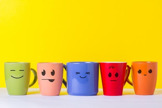 Un sacco di tazze colorate con facce buffe su uno sfondo giallo. il concetto di compagnia amichevole, famiglia numerosa, incontro di amici per una tazza di tè o caffè, festa del papà, ufficio, festa del capo.