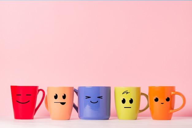 Un sacco di tazze multicolori con facce buffe su uno sfondo rosa. il concetto di compagnia amichevole, famiglia numerosa, incontro di amici per una tazza di tè o caffè, festa del papà, ufficio, festa del capo.