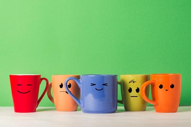 Un sacco di tazze multicolori con facce buffe su uno sfondo verde. il concetto di compagnia amichevole, famiglia numerosa, incontro di amici per una tazza di tè o caffè, festa del papà, ufficio, festa del capo.