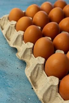 Un sacco di uova marroni di pollo su una superficie blu