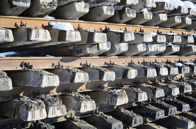 Un sacco di vecchie rotaie e dormienti sono accatastati in un magazzino ferroviario in inverno.