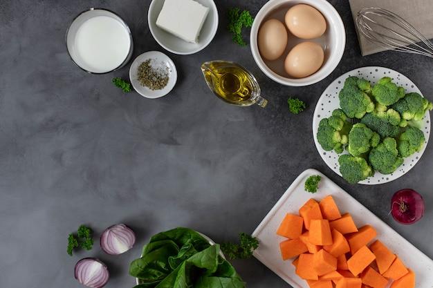 Un sacco di verdure crude, spezie e olio d'oliva. cucinare il concetto di cibo sano. sfondo scuro, copia spazio
