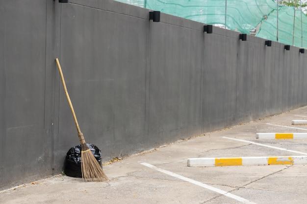 Un sacco nero di spazzatura e vecchia scopa contro un muro grigio., con copia spazio per il testo.