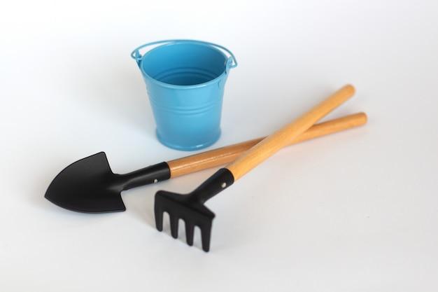 Un secchio blu colorato con pala e rastrello su bianco