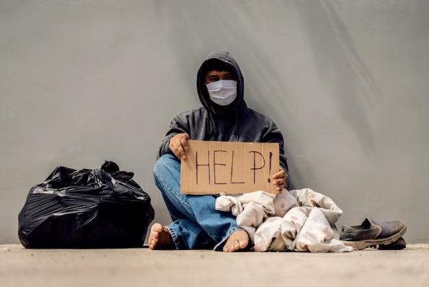 Un senzatetto disoccupato per strada a causa del virus corona brama e ha bisogno di aiuto