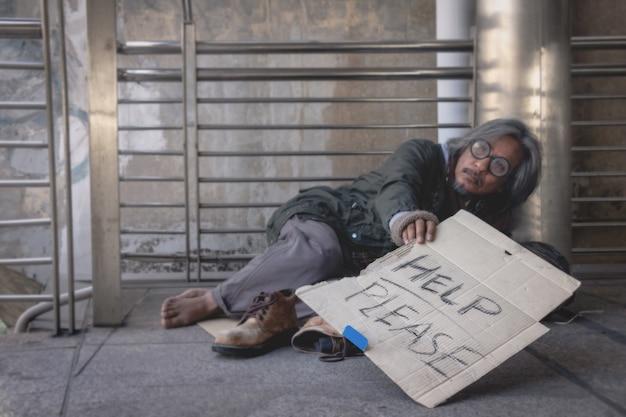 Un senzatetto è seduto sulla passerella in città. lui è l'etichetta