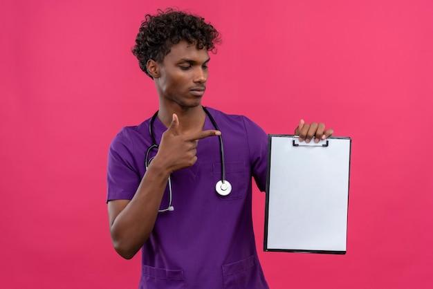 Un serio giovane bel dottore di carnagione scura con capelli ricci che indossa l'uniforme viola con lo stetoscopio che punta con il dito indice negli appunti con un foglio di carta bianco