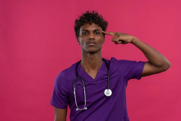 Un serio giovane medico dalla carnagione scura bello con capelli ricci che porta l'uniforme viola con lo stetoscopio che indica con l'indice sulla testa