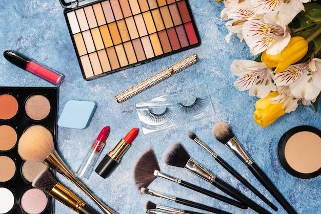 Un set di cosmetici decorativi, pennelli per il trucco e un mazzo di fiori sul blu