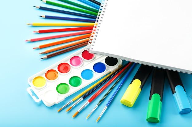 Un set di materiale scolastico per l'apprendimento e lo sviluppo creativo su sfondo blu. spazio libero sull'album bianco, la vista dall'alto
