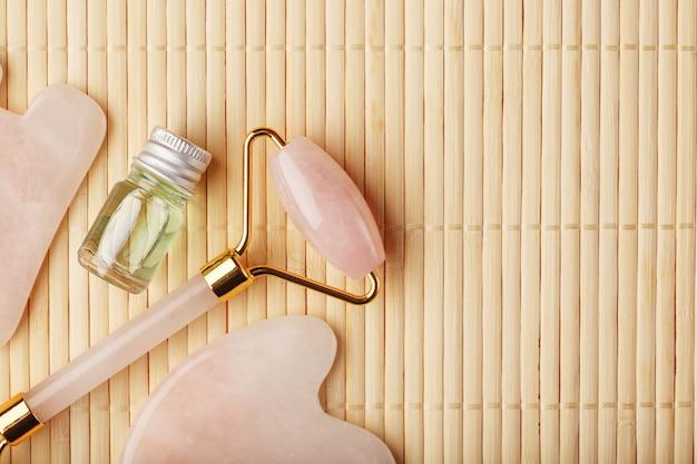 Un set di strumenti per la tecnica di massaggio del viso gua sha realizzato in quarzo rosa naturale. rullo, pietra di giada e olio in un barattolo di vetro, su uno sfondo di paglia per la cura del viso e del corpo.