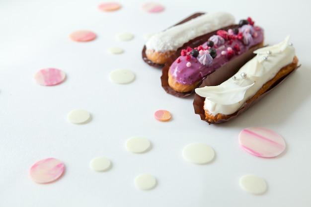 Un set di tre eclair con diversi ripieni e design isolato su una superficie bianca decorata con gocce di cioccolato bianco