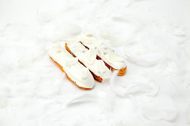 Un set di tre eclairs con decorarion di cioccolato bianco