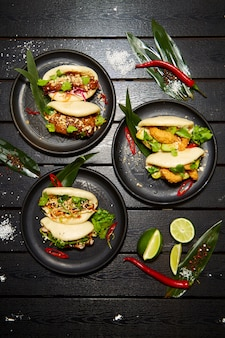 Un set di tre piatti asiatici su piatti neri su un tavolo di legno decorato con lime, peperoncino e farina. bao appetitoso con verdure e carne