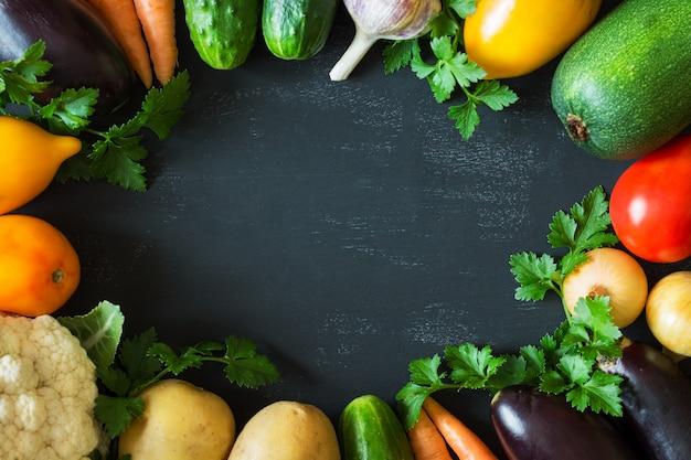 Un set di verdure fresche (cetrioli, pomodori, cavoli, carote, aglio, cipolle), disposti in un cerchio su uno sfondo nero