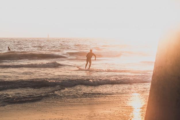 Un surfista che corre sulla spiaggia