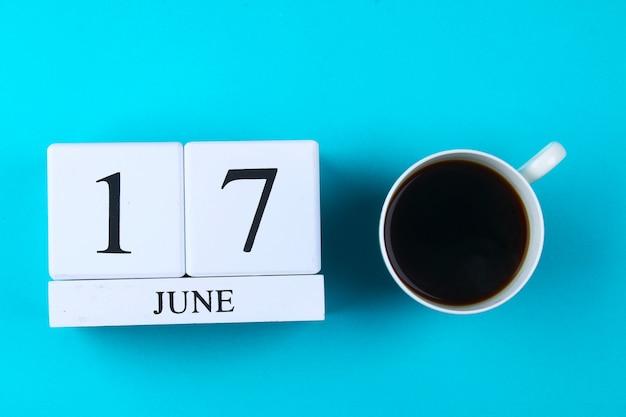 Un taccuino di legno con una data il 17 giugno e una tazza di caffè su uno sfondo blu pastello. festa del papà.