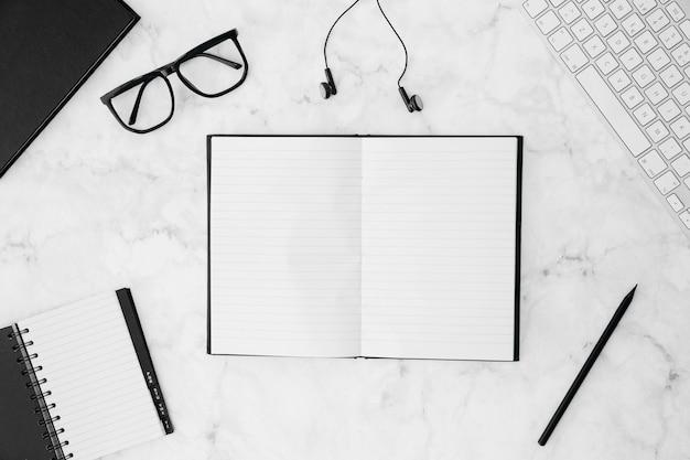 Un taccuino in bianco aperto con gli occhiali; diario; matita; auricolare; tastiera sulla scrivania bianca