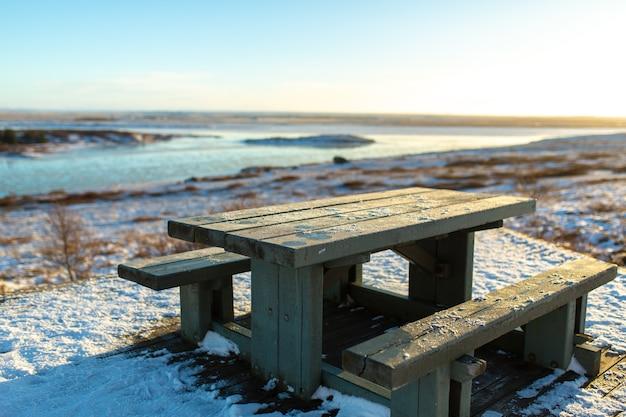 Un tavolo con una panca per riposare coperto di neve in inverno in islanda