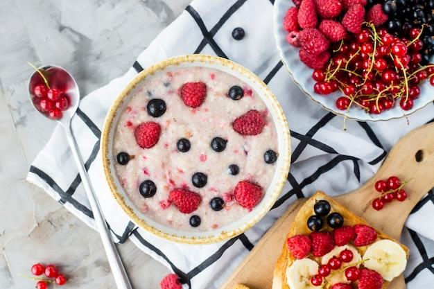 Un tavolo con una sana colazione estiva - farina d'avena con frutti di bosco, ribes e lamponi