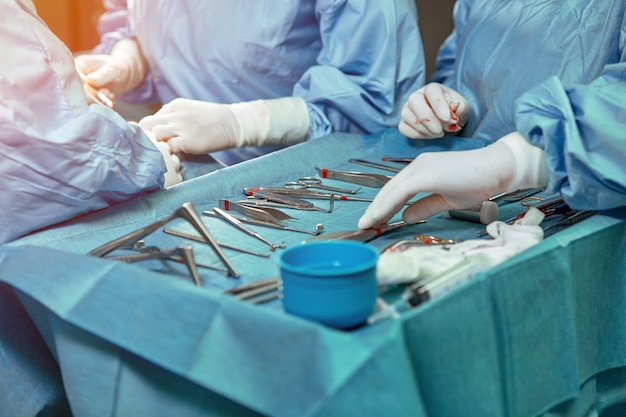Un tavolo sterile per sala operatoria con strumenti per chirurgia situato su di esso. le mani dei chirurghi in guanti bianchi cambiano gli strumenti.