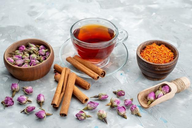 Un tè con vista frontale con cannella insieme a fiori viola su tutta la bevanda dell'acqua del tè della scrivania
