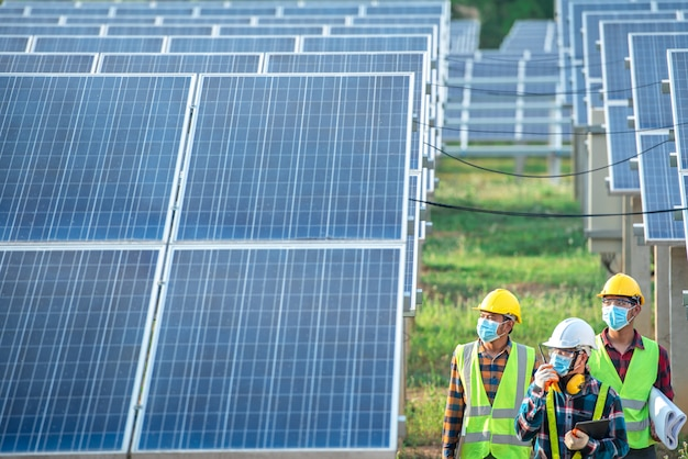 Un team di ingegneri e tre architetti asiatici hanno camminato per visitare il pannello solare. team di ingegneri che indossano maschere mediche per proteggere il virus corona (covid-19). gli ingegneri asiatici guardano i pannelli solari.