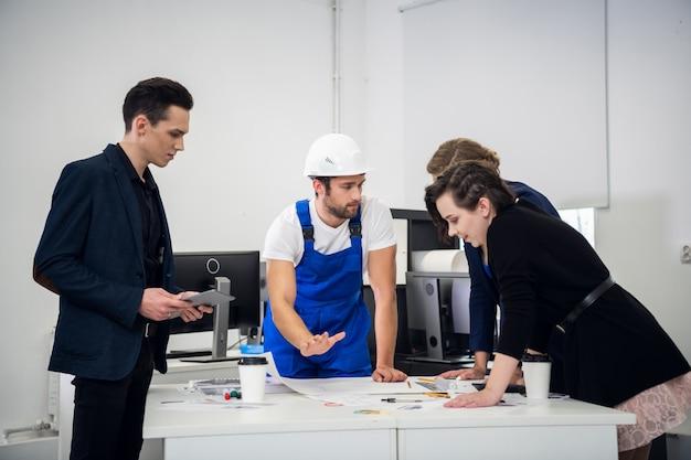 Un team di progettisti di costruzioni incontra un ingegnere in ufficio per discutere del progetto attuale