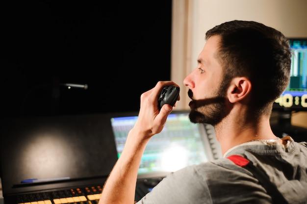 Un tecnico dell'illuminazione lavora con il controllo dei tecnici delle luci durante lo spettacolo. mixer professionale, consolle di missaggio. attrezzature per concerti.