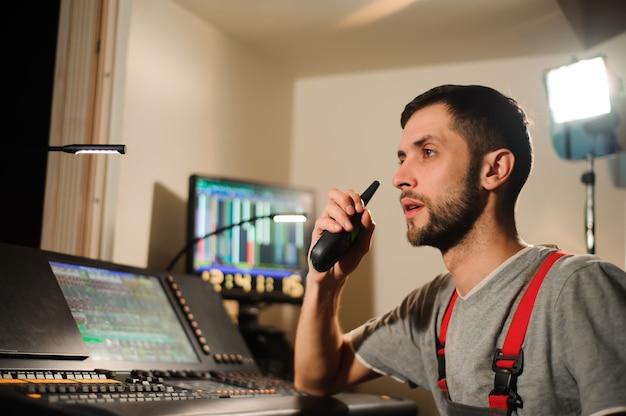 Un tecnico dell'illuminazione lavora con il controllo dei tecnici delle luci durante lo spettacolo. mixer professionale, consolle di missaggio. attrezzature per concerti