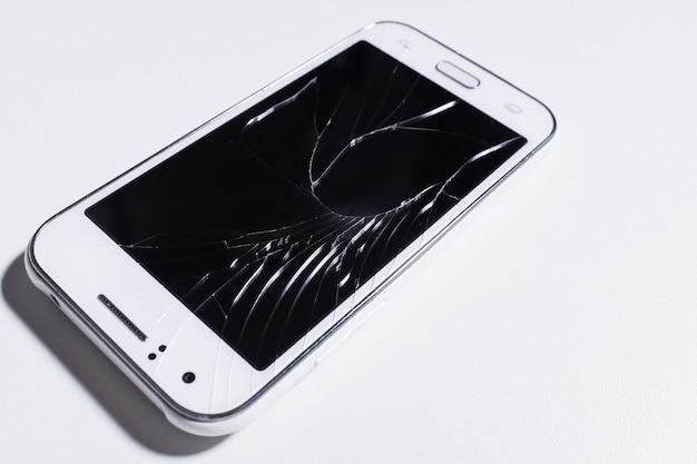 Un telefono cellulare bianco è schermo rotto su white.blank per lo spazio della copia.