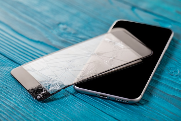 Un telefono cellulare nero è schermo rotto su fondo di legno.