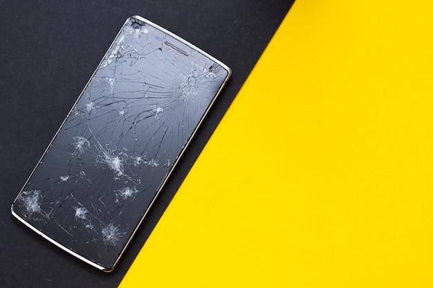 Un telefono rotto su sfondo giallo e nero. dispositivo schiacciato con schermo rotto che rappresenta un incidente.