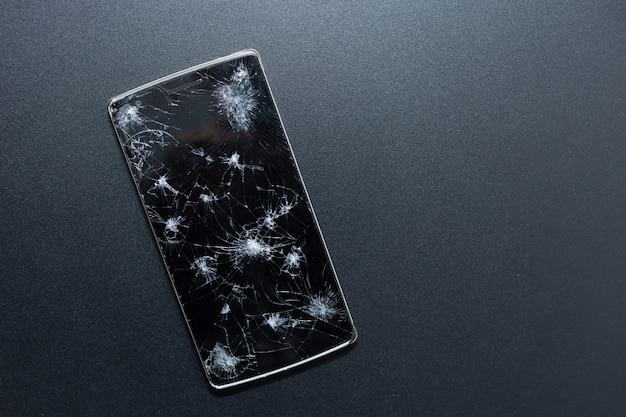 Un telefono rotto su sfondo nero. dispositivo schiacciato con schermo rotto che rappresenta un incidente. schermo strutturato con danno. vetro scuro di uno schermo, rotto.