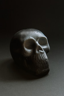 Un teschio su uno sfondo scuro, disteso su una superficie piana