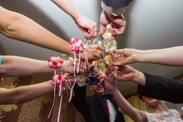 Un tintinnio di bicchieri al matrimonio. ospiti del matrimonio bevendo champagne