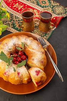 Un tondo della torta della ciliegia di vista superiore formato all'interno della zolla marrone con il tè sul dolce scuro dello zucchero del biscotto della torta dello scrittorio