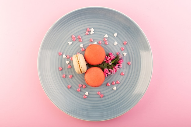 Un tondo di macarons francesi con vista dall'alto formato all'interno del piatto blu sul colore rosa del dolce del biscotto della torta della tavola