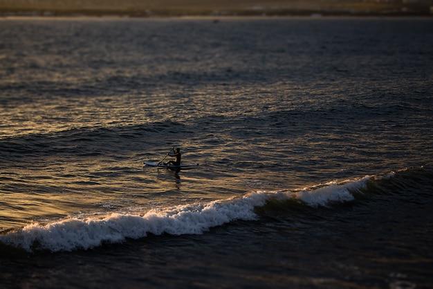 Un tramonto luminoso, raggi che cadono sulla superficie del mare, grandi onde di schiuma che si dirigono verso le rocce e surfisti in sup, paesaggi meravigliosi nella città turistica di gelendzhik