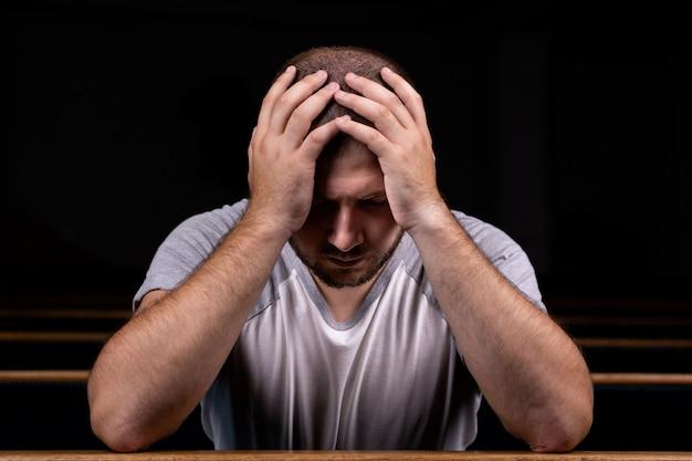 Un triste uomo cristiano in camicia bianca è seduto e prega con umile cuore nella chiesa