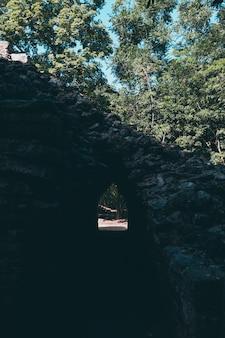 Un tunnel tra le rovine maya con alberi dietro in coba