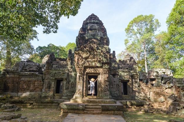 Un turista che visita le rovine di angkor in mezzo alla giungla, il complesso del tempio di angkor wat, destinazione cambogia. donna con cappello tradizionale, vista posteriore.