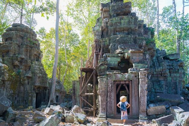 Un turista che visita le rovine di angkor in mezzo alla giungla