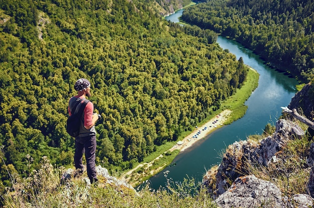 Un turista con uno zaino su una roccia che gode di una vista sulla valle del fiume