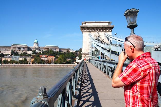 Un turista, in piedi su un ponte pedonale, scatta foto del palazzo del parlamento a budapest