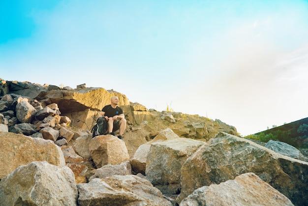Un turista si siede su una grande pietra su roccia in estate.